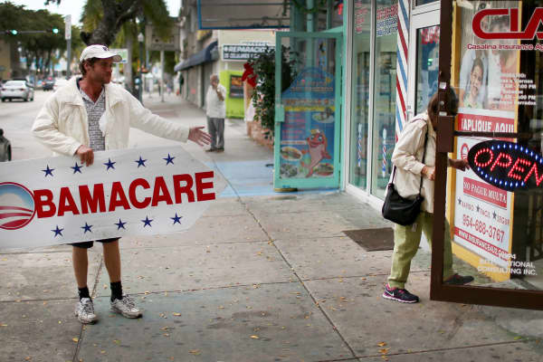 In this 2015 file photo, a man holds a sign directing people to an insurance company where they can sign up for the Affordable Care Act.