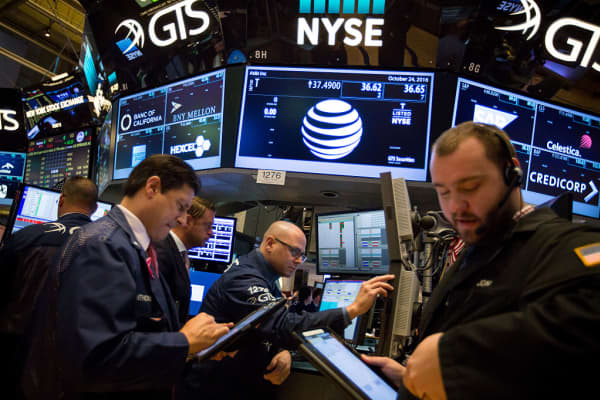 AT&T signage is displayed on a monitor above traders working on the floor of the New York Stock Exchange.