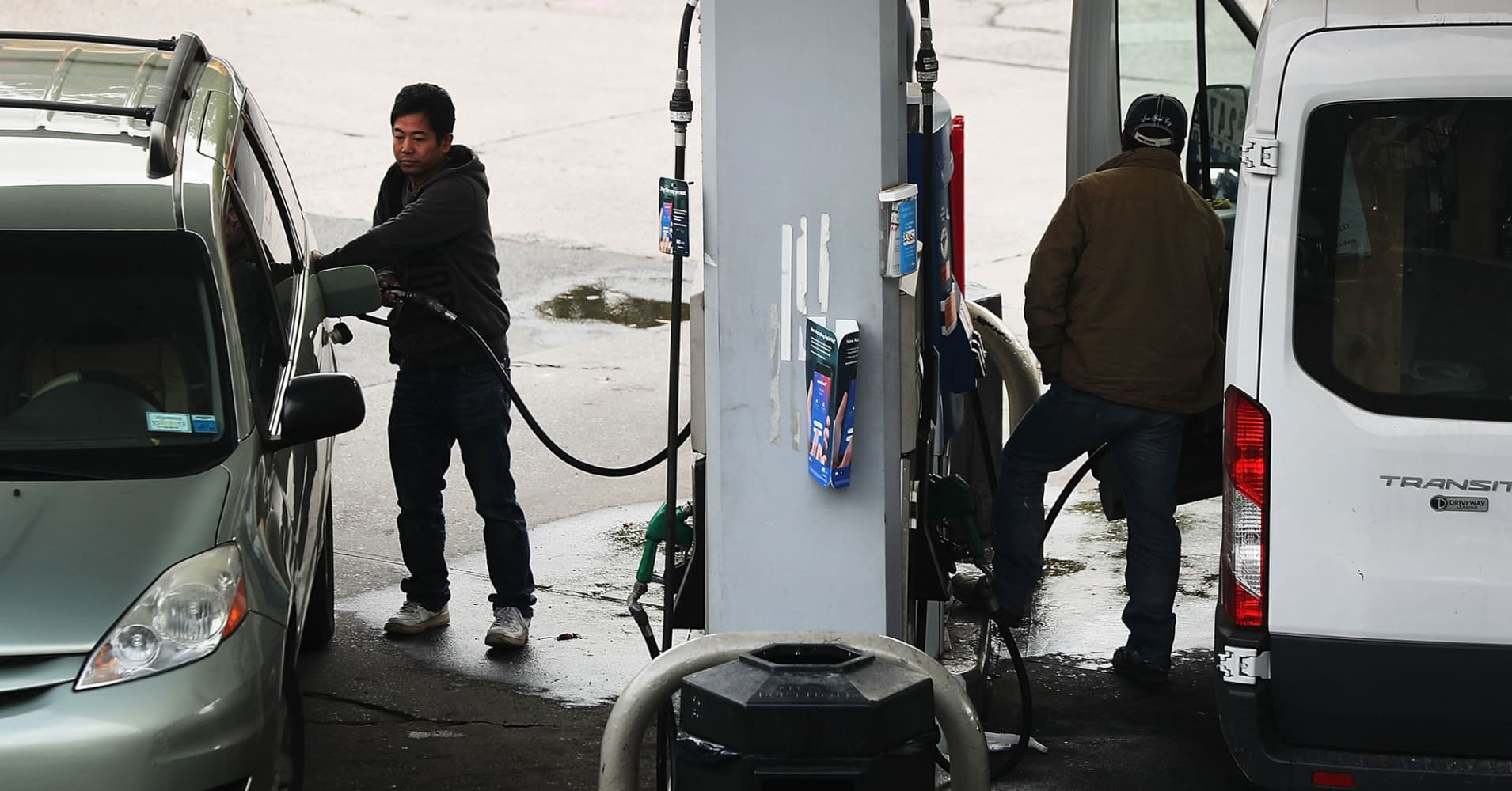 People use an Exxon gas station in Brooklyn, New York.