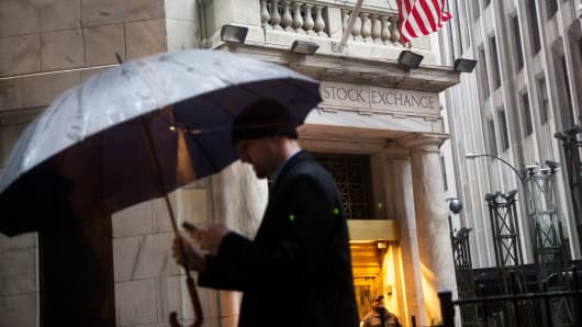 A pedestrian carries an umbrella while walking along Wall Street past the New York Stock Exchange in New York.