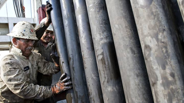 Workers guide a section of drill pipe into a rack after it was removed from a natural gas well being drilled in the Eagle Ford shale in Karnes County, Texas.