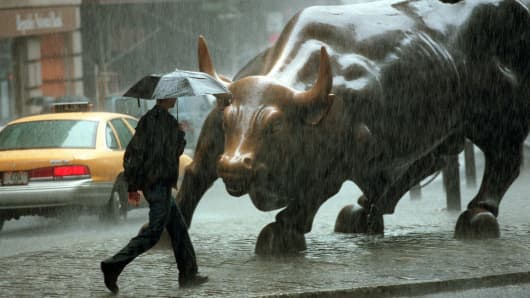 A pedestrian passes in front of a statue of a bull in the Wall Street area in New York City.