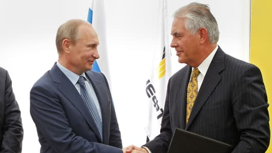 Russian President Vladimir Putin, center, and then-Exxon Mobil CEO Rex Tillerson shake hands at a signing ceremony of an agreement between state-controlled Russian oil company Rosneft and Exxon Mobil corporation at the Black Sea port of Tuapse, southern Russia, June 15, 2012.