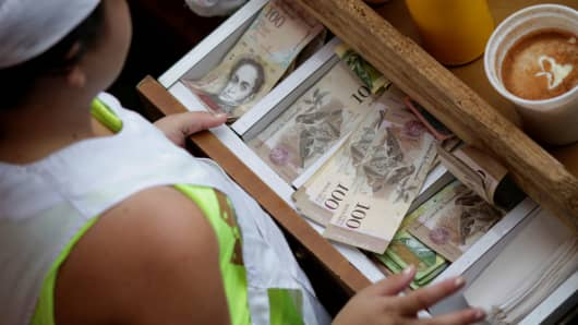A cashier receives Venezuelan bolivar notes at a market in downtown Caracas, Venezuela, December 7, 2016.