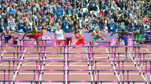 China's Liu Xiang (C) falls while competing in the men's 110m hurdles heats at the athletics event of the London 2012 Olympic Games on August 7, 2012 in London.