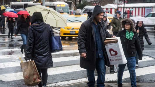 People walk along the sidewalk in the rain in New York.