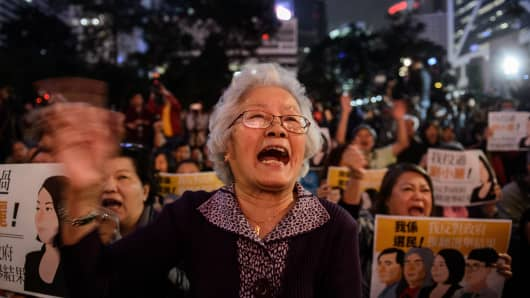Pro-democracy protesters react during a rally in Hong Kong on December 11, 2016, against a crackdown on pro-democracy lawmakers and an electoral system skewed towards Beijing ahead of elections for a new city leader.