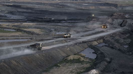 Dump trucks travel through the open pit at the Tavan Tolgoi coal deposit in Tsogtsetsii, Ömnögovi Province, Mongolia.