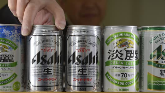 A liquor shop owner stocks cans of Asahi Breweries Ltd. Asahi Super Dry beer in Kawasaki, Kanagawa Prefecture, Japan, on Wednesday, Jan. 9, 2013.