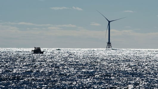 A boat passes one of the wind turbines of the Block Island Wind Farm on October 14, 2016 off the shores of Block Island, Rhode Island.