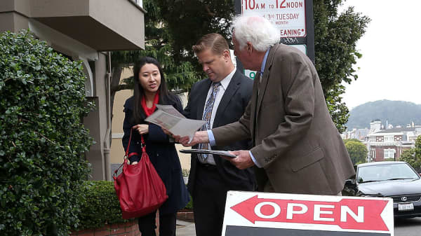 Real estate agent hands out information on a home for sale during an open house in San Francisco, California.
