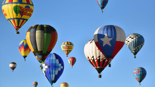 Dozens of balloons hover in the sky during the Mass Ascencion at the opening of the International Balloon Fiesta at Balloon Fiesta Park in Albuquerque, New Mexico.
