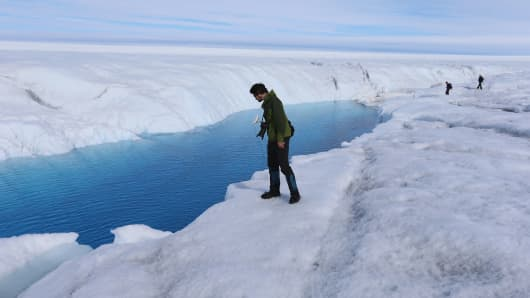 A Ph.D. student at the University of Washington looks at a meltwater stream on the Glacial Ice Sheet, Greenland.