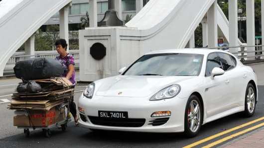 A woman pushes a trolley of recycle waste past a luxury car on the street in Singapore on March 4, 2014.
