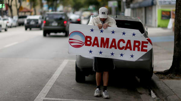 A man holds a sign directing people to an insurance company where they can sign up for the Affordable Care Act.