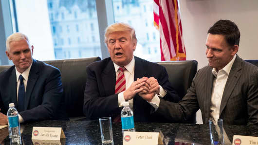 (L to R) Vice President-elect Mike Pence looks on as President-elect Donald Trump shakes the hand of Peter Thiel during a meeting with technology executives at Trump Tower, December 14, 2016 in New York City.