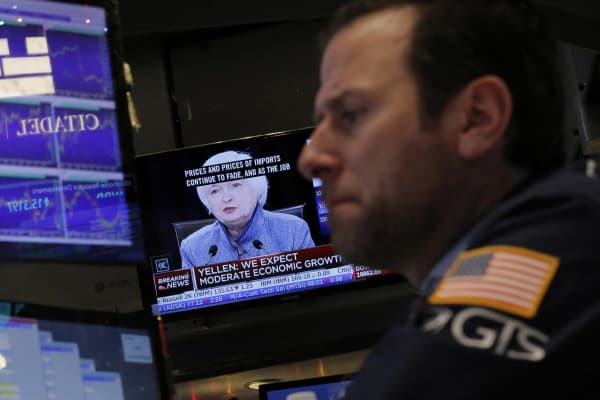 A trader works on the floor of the New York Stock Exchange (NYSE) as a television screen displays coverage of U.S. Federal Reserve Chairman Janet Yellen shortly after the announcement that the U.S. Federal Reserve will hike interest rates in New York, U.S.