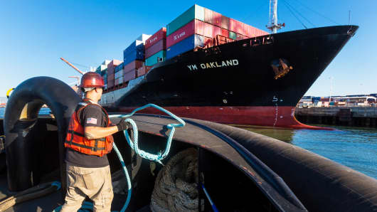 The Yang Ming Marine Transport Corp. Oakland cargo ship is guided into the Port of Oakland by a pair of AmNav tugboats as an engineer tends to mooring lines in Oakland, California.