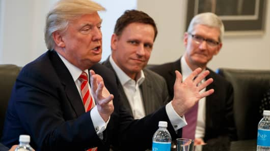 Apple CEO Tim Cook, right, and PayPal founder Peter Thiel, center, listen as President-elect Donald Trump speaks during a meeting with technology industry leaders at Trump Tower in New York, Wednesday, Dec. 14, 2016.