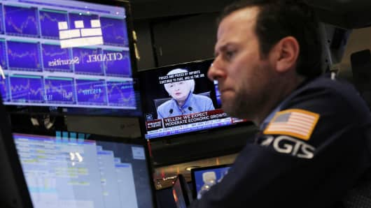 A trader works on the floor of the New York Stock Exchange as a television screen displays coverage of U.S. Federal Reserve Chairman Janet Yellen shortly after the announcement that the U.S. Federal Reserve will hike interest rates in New York, December 14, 2016.