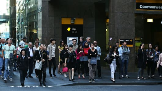 Pedestrians walk past a branch of Commonwealth Bank in the central business district in Sydney, Australia.