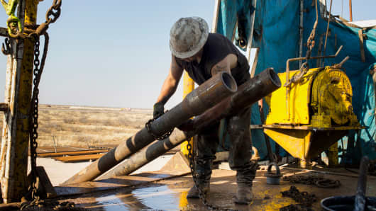 A worker prepares to lift drills by pulley to the main floor of a drilling rig in the Permian basin.