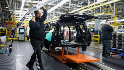 An employee carries a headliner to be installed onto a vehicle at the General Motors assembly plant in Arlington, Texas.