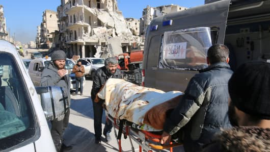 Men push an evacuee on a stretcher as vehicles wait to evacuate people from a rebel-held sector of eastern Aleppo, Syria December 15, 2016.
