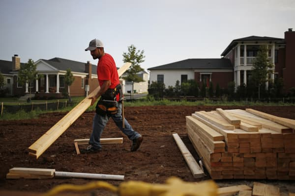A contractor moves lumber for a house under construction in the Norton Commons subdivision of Louisville, Kentucky.