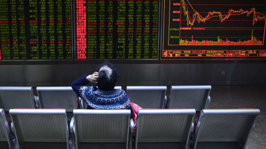 An investor rests on a chair in front of screens showing stock market movements at a securities company in Beijing.
