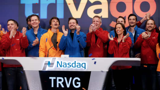 Trivago co-founder and CEO Rolf Schromgens (C) applauds after ringing the opening bell on the Nasdaq Market Site as Trivago was listed during an initial public offering in New York, December 16, 2016.