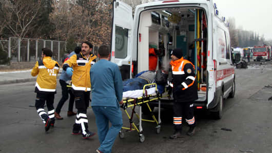 A wounded man is carried to an ambulance after a bus was hit by an explosion in Kayseri, Turkey.