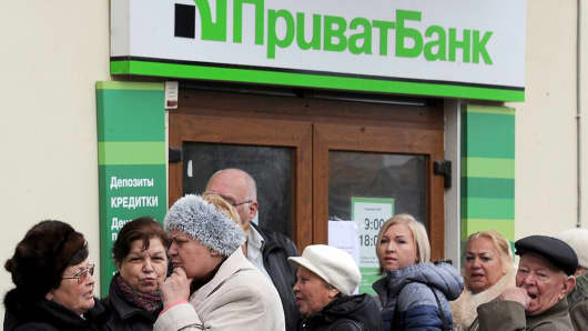 People queue outside a PrivatBank branch in Ukraine.