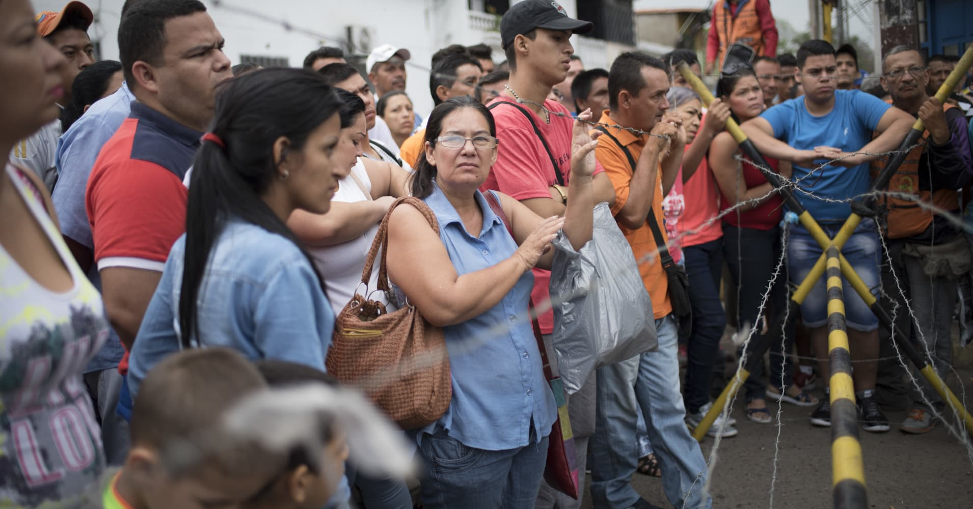People wait to cross the border into Colombia at a checkpoint in Urena, Venezuela, on Sunday, Dec. 18, 2016.