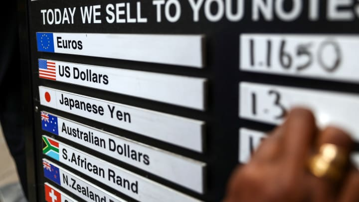 An employee updates the British pound and U.S. dollar currency exchange rate on a board outside outside a foreign currency exchange bureau