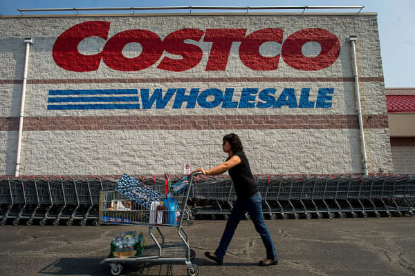 A customer pushes a cart of purchased items outside a Costco Wholesale Corp. store in Hackensack, New Jersey, U.S.