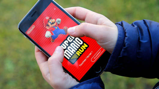 A child shows the screen of his smartphone with the start screen of 'Super Mario Run,' a side-scrolling adventure game featuring Nintendo Co.'s Mario popular Italian mascot, in Paris on December 17, 2016.