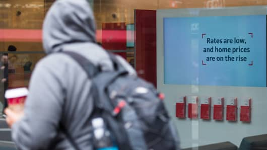 A pedestrian walks past a sign that reads 'Rates are low and home prices are on the rise' inside a Santander bank branch in New York,