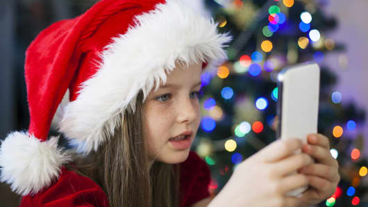 Girl in Santa's hat with Christmas present - smartphone