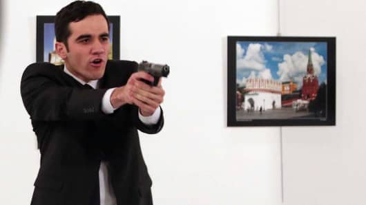 An unnamed gunman points his gun, after shooting the Russian Ambassador to Turkey, Andrei Karlov, at a photo gallery in Ankara, Turkey, Monday, Dec. 19, 2016.