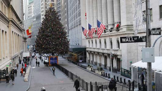Pedestrians walk near the New York Stock Exchange on December 19, 2016.