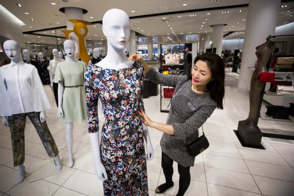An employee arranges a dress on a mannequin in a Nordstrom store.