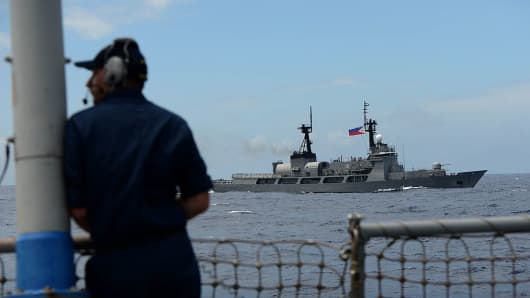 U.S. Navy personnel looks at Philippine Navy vessel BRP Ramon Alcaraz during a bilateral maritime exercise in the South China Sea.