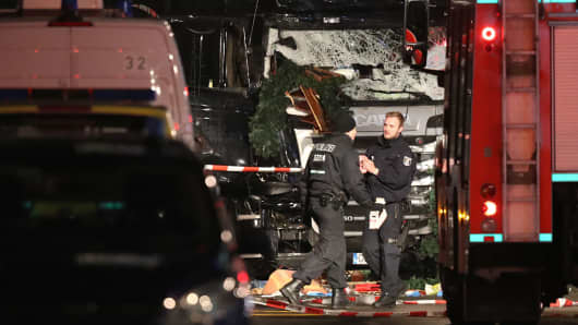 Security and rescue workers tend to the area after a lorry truck ploughed through a Christmas market  on December 19, 2016 in Berlin, Germany.
