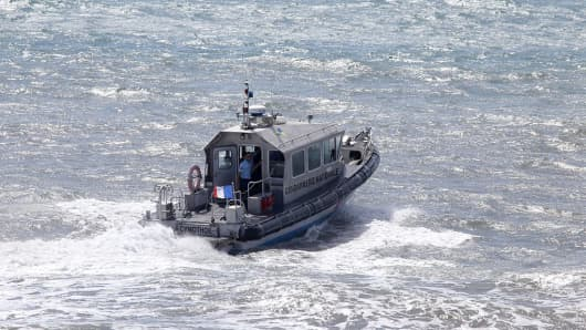 French maritime gendarmes in a boat take part in the search for wreckage from the missing MH370 plane off of Saint-Marie on the French island of La Reunion on August 14, 2015.