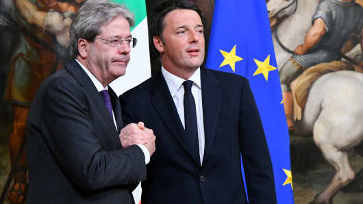 Former Prime Minister Matteo Renzi (R) and Italy's newly appointed Prime Minister Paolo Gentiloni pose during a swearing in ceremony at the Palazzo Chigi on December 12, 2016