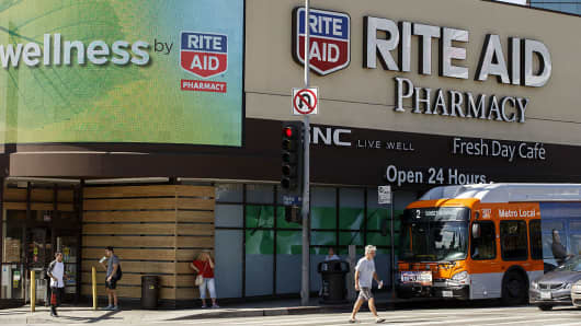 Pedestrians walk in front of a Rite Aid Corp. store in Los Angeles, California, U.S., on Tuesday, Sept. 20, 2016.