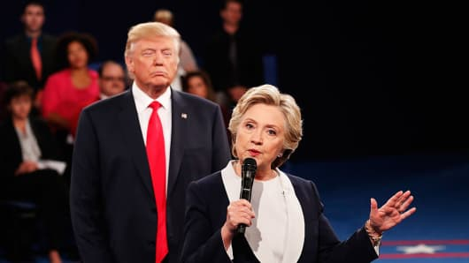 Hillary Clinton speaks as Donald Trump looks on during the town hall presidential debate at Washington University on October 9, 2016, in St Louis.