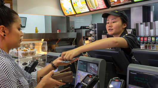 McDonald's fast food restaurant cashier employee giving change to a customer.