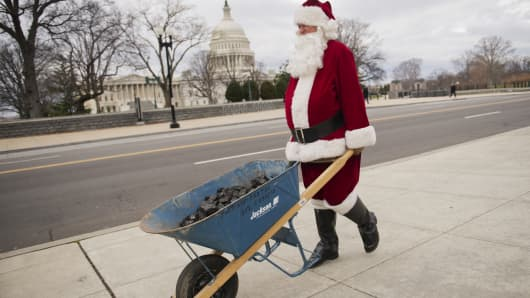 Santa Claus, also known as Sam McCrea, makes his way along 1st St., en route to the Capitol to deliver coal as a Christmas gift to Congress for their inability to reach a solution on the 'fiscal cliff.'